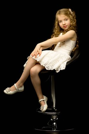 Little girl is sitting on a chair