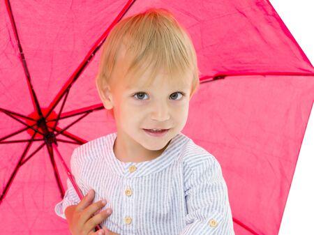 A cute little boy took cover under an umbrella. Foto de archivo - 129809735