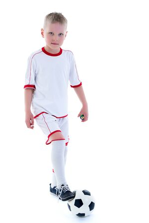 A little boy wearing a pure white t-shirt is playing with a soccer ball
