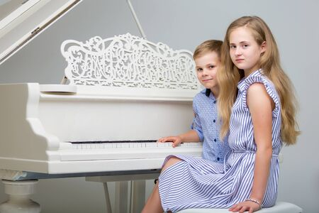 Two little kids, girl and boy playing piano in living room