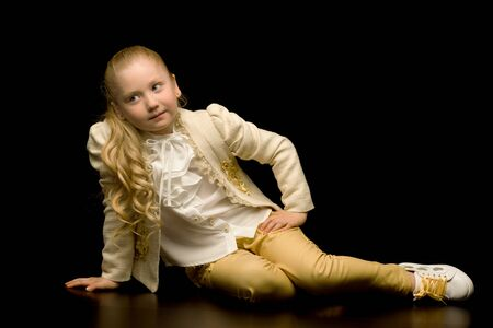 A little girl is sitting in the studio on the floor