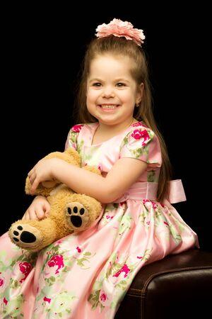 Little girl with a teddy bear on a black background.