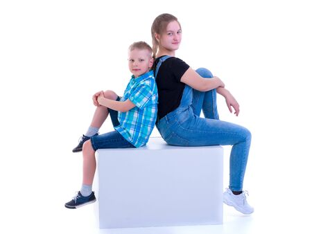 A brother and sister, a girl and a boy are photographed in a studio