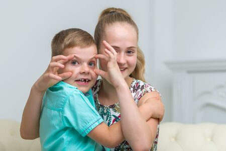 Brother and sister, boy and girl posing in the studio. Friendship