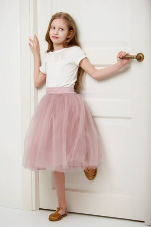 A little girl is standing by the door.