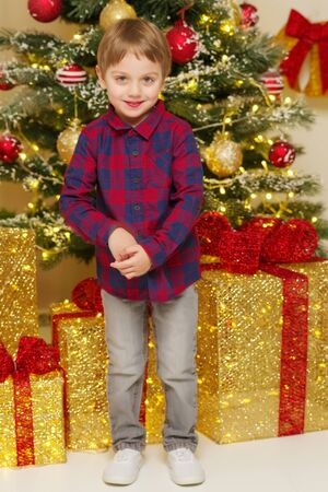 A little boy near the Christmas tree with a gift.