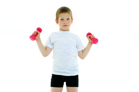 A little boy is lifting dumbbells. Imagens