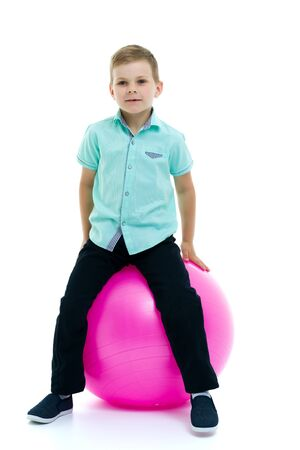 Cute boy playing with fit ball isolated on white