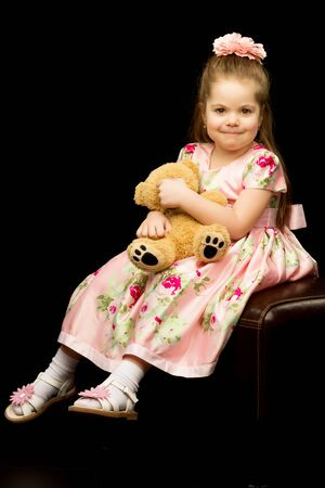 Little girl with a teddy bear on a black background. Stockfoto - 131364857
