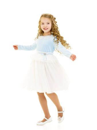 A little girl in a dress is spinning.