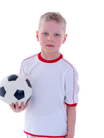 A little boy wearing a pure white t-shirt is playing with a socc