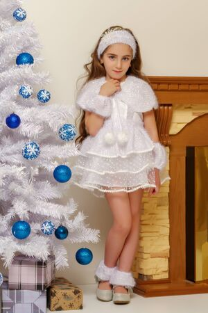 Beautiful little girl near the Christmas tree.