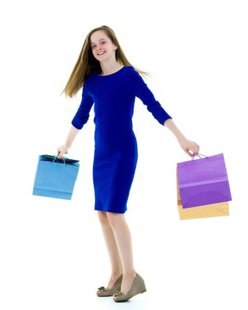 Teenager girl shopping in a store with large paper bags.