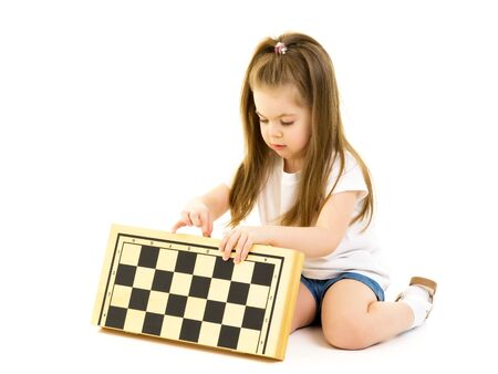 Little girl playing chess. Isolated on white background.