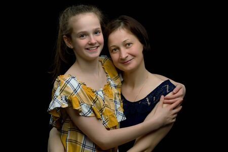 Mom and daughter in the studio on a black background. Stock Photo