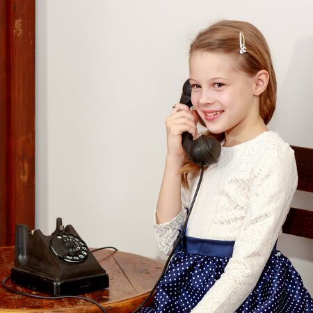 Girl talking on old phone.