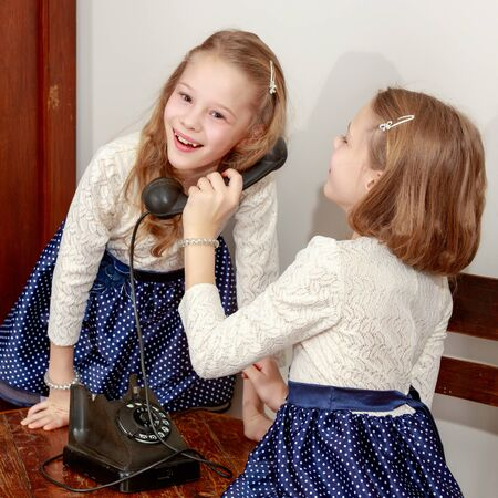 Two sisters talking on old phone