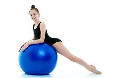 little girl doing exercises on a big ball for fitness. Stockfoto