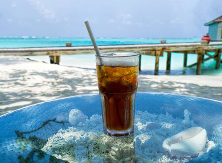 A glass of cold cocktail on a table on the beach in a restaurant Banco de Imagens