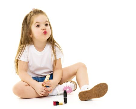 Little girl paints lips with moms lipstick.
