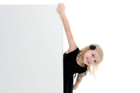 A little girl is looking from behind an empty banner. Stockfoto
