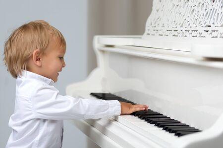 Little boy in studio near white piano.