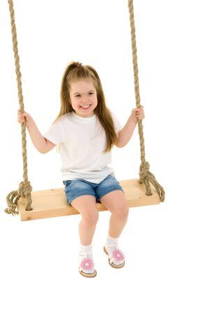 Little girl swinging on a swing Stock Photo