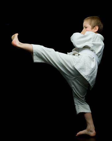 A little boy in a white kimono fulfills blows Banco de Imagens
