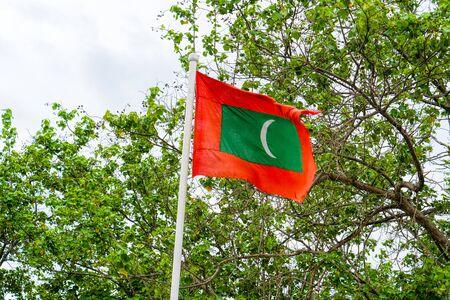 Maldives national flag on blue sky background
