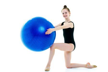 little girl doing exercises on a big ball for fitness. 版權商用圖片