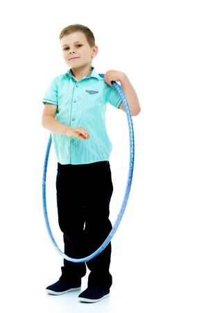A little boy is playing with a hoop.