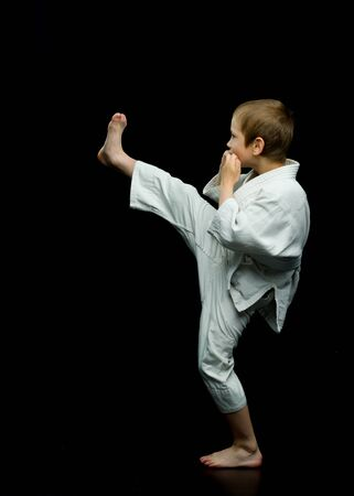 A little boy in a white kimono fulfills blows