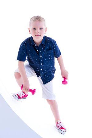 A little boy is lifting dumbbells. Stok Fotoğraf