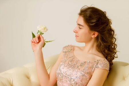 Teen girl sitting on the couch holding a flower in her hand.