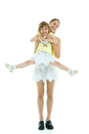 Beautiful young girl holding her little sister in her arms.