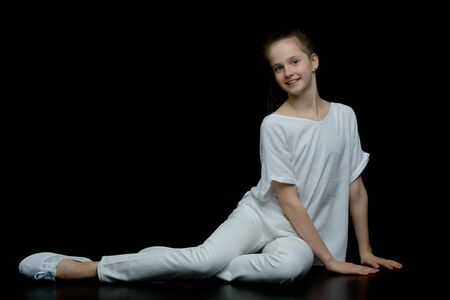 A little girl is kneeling on a black background in the studio.