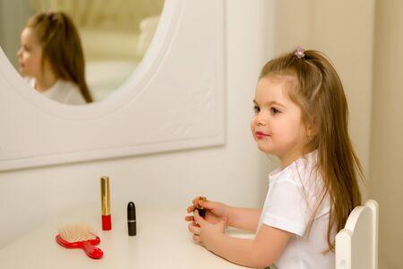 A little girl near the mirror paints lipstick lips