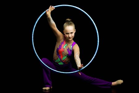 A girl gymnast performs an exercise with a hoop. Reklamní fotografie
