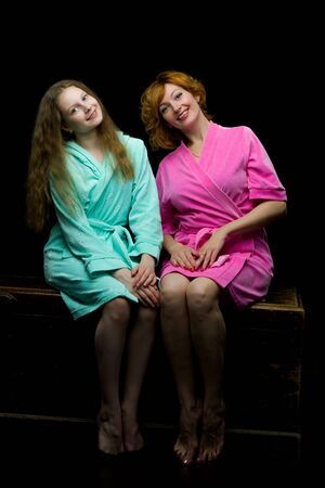 Daughter and mother in bathrobes posing in the studio.
