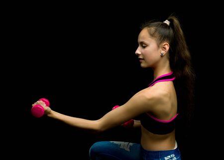 Teenage girl with dumbbells in hands