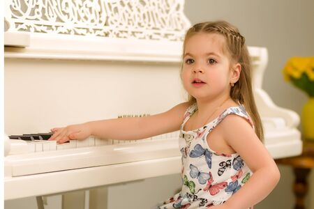 Beautiful little girl is playing a white grand piano.