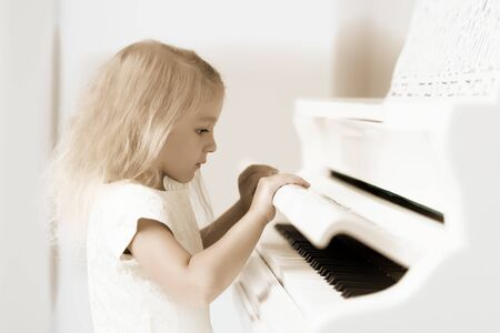 The girl is at the white grand piano. Stok Fotoğraf - 131822956