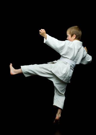 A little boy in a white kimono fulfills blows Фото со стока