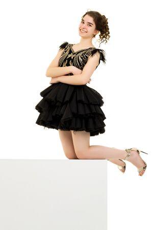 Teenage girl posing studio on a white cube. Фото со стока