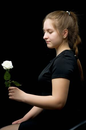 Little girl with a white flower on a black background. Stock fotó