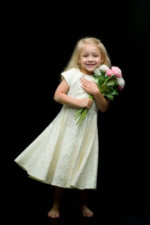 Little girl with a bouquet of flowers on a black background.