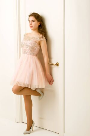 Girl teenager in a smart dress standing near the white door.
