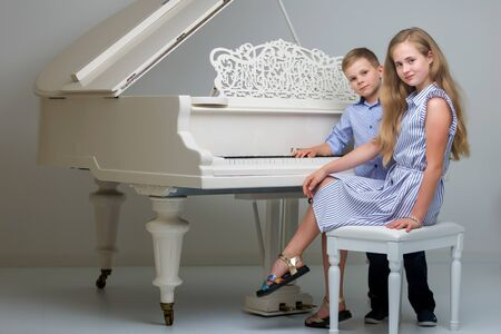 little girl and boy playing piano in living room Imagens
