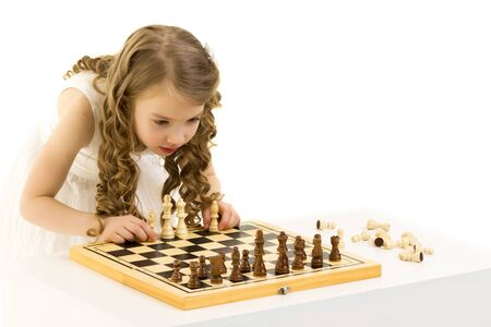 A little girl is playing chess. Archivio Fotografico