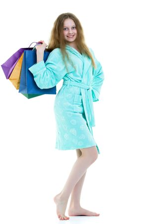 Cheerful girl in a short robe waving multicolored paper bags. Th Stock Photo
